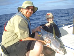 Image of James Nelson landing a yellowfin tuna for a client