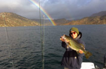 "SDFish member ""Patch Ellis"" with a nice bass at San Vicente with a brilliant double rainbow in the background"